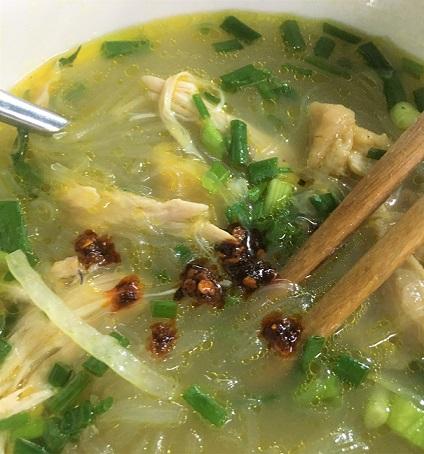 牛肉のスープに米の麺を入れ鶏肉を投入したフエの麺料理の写真