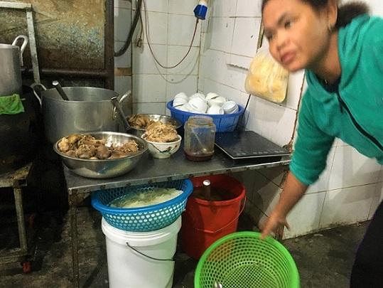 フエの食堂に準備されているキノコや牛骨などの食材と、そこで働いているベトナム人の女性の写真。