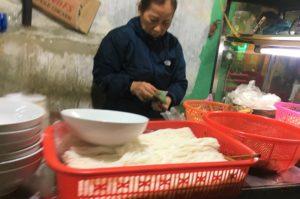 会計を担当している安食堂のおばちゃんがベトナム料理の仕込みをしている写真