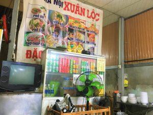 フエのベトナムB級グルメ食堂の店内の写真|テレビやメニュー表、食器や飲み物類がある